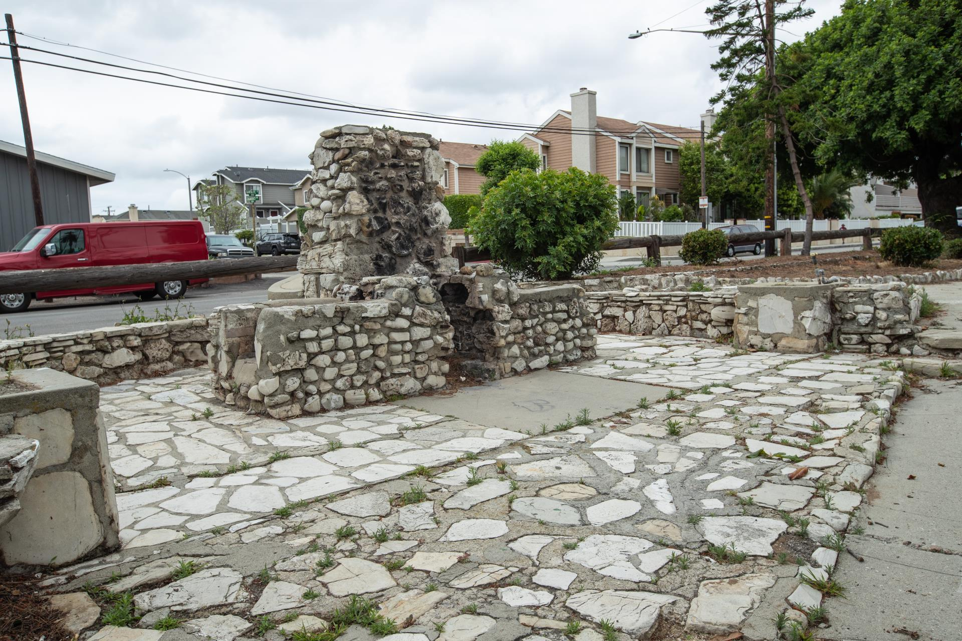 Stone structure across the street from houses and cars